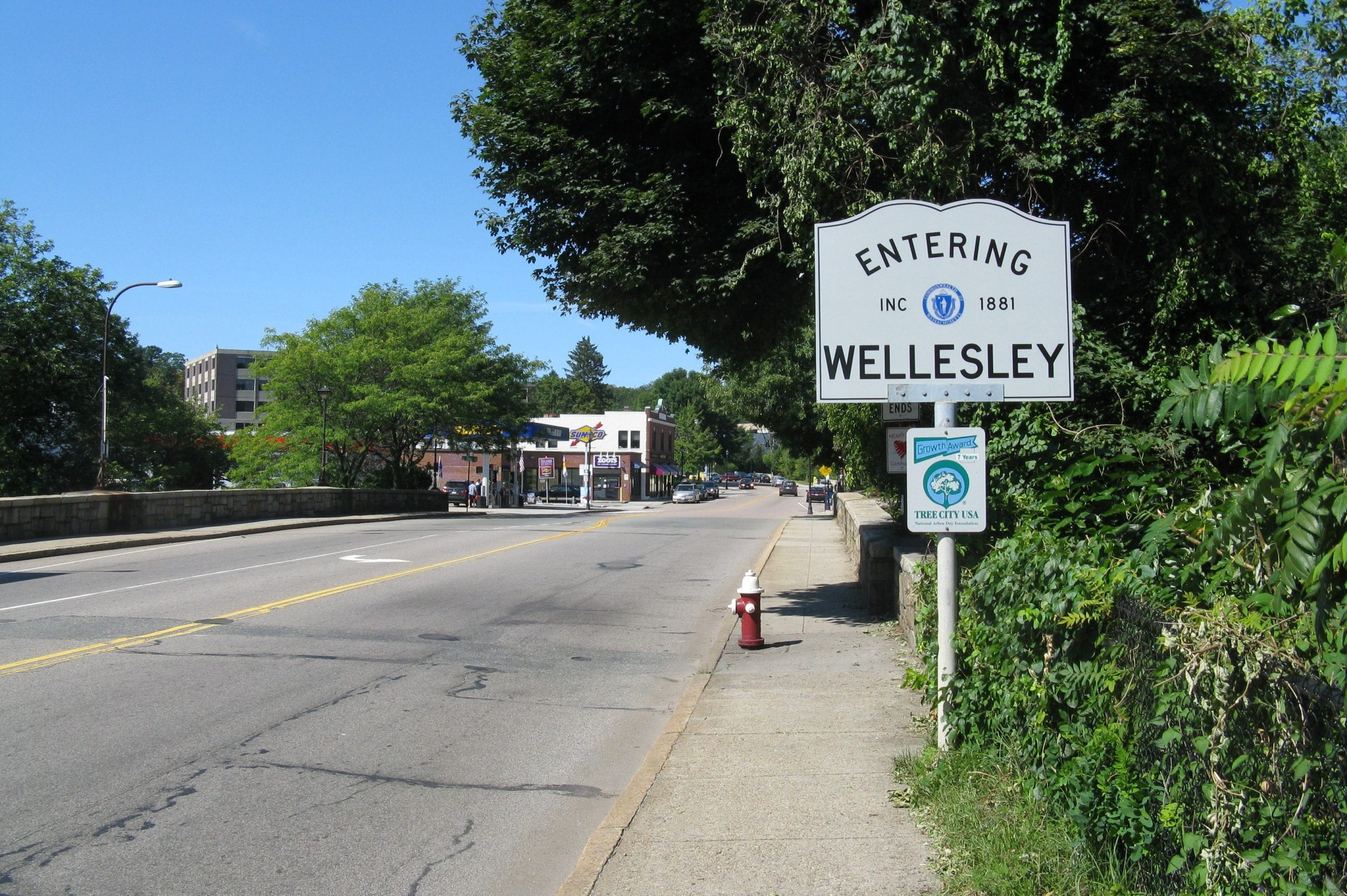 A sign on the road that says Entering Wellesley in Massachusetts.